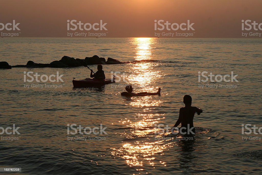 sunset over people playing in the water royalty-free stock photo