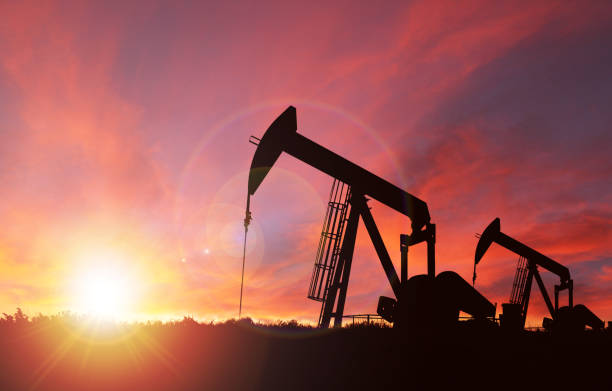 sunset over pumpjack silhouette with copy space - crude stock pictures, royalty-free photos & images