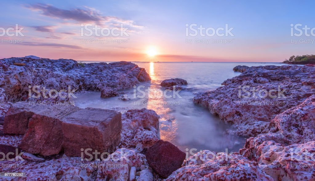 Sunset over rocky beach stock photo
