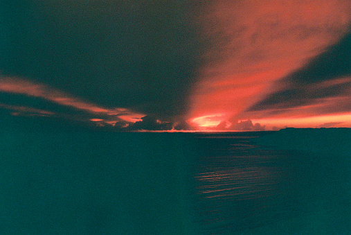 Sunbeams through cloud as the sun sets, with the sea in the backround. Dorset/Devon border UK, 35mm Lomography Redscale film