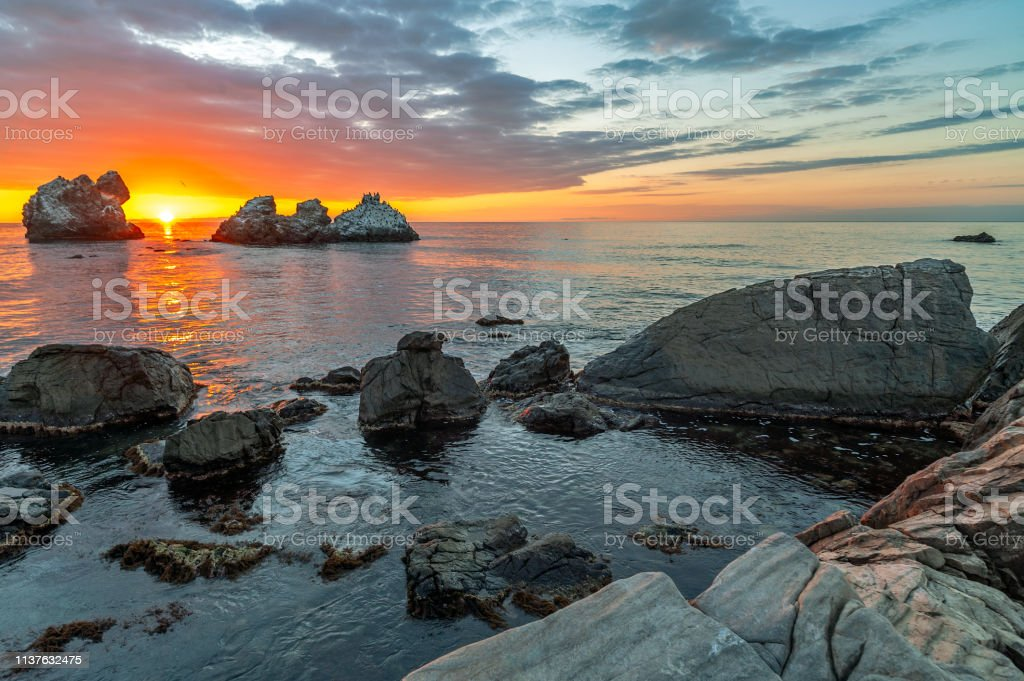 Sunset over sea and stone shore stock photo