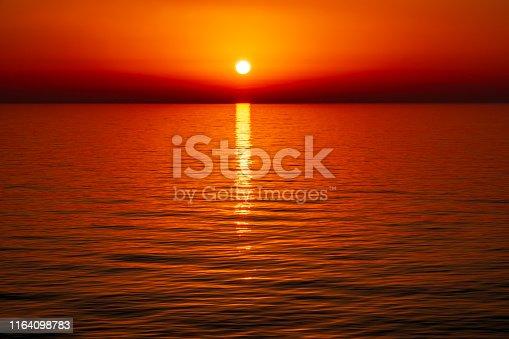 The sun setting over the horizon at sea