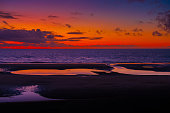 A colourful sunset over the horizon, at sea. Reflections in beach pools.
