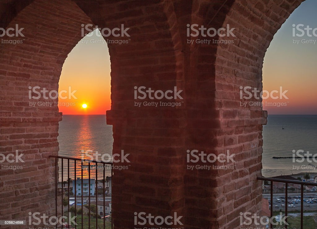 Sunset Over Sea Through Medieval Arch stock photo