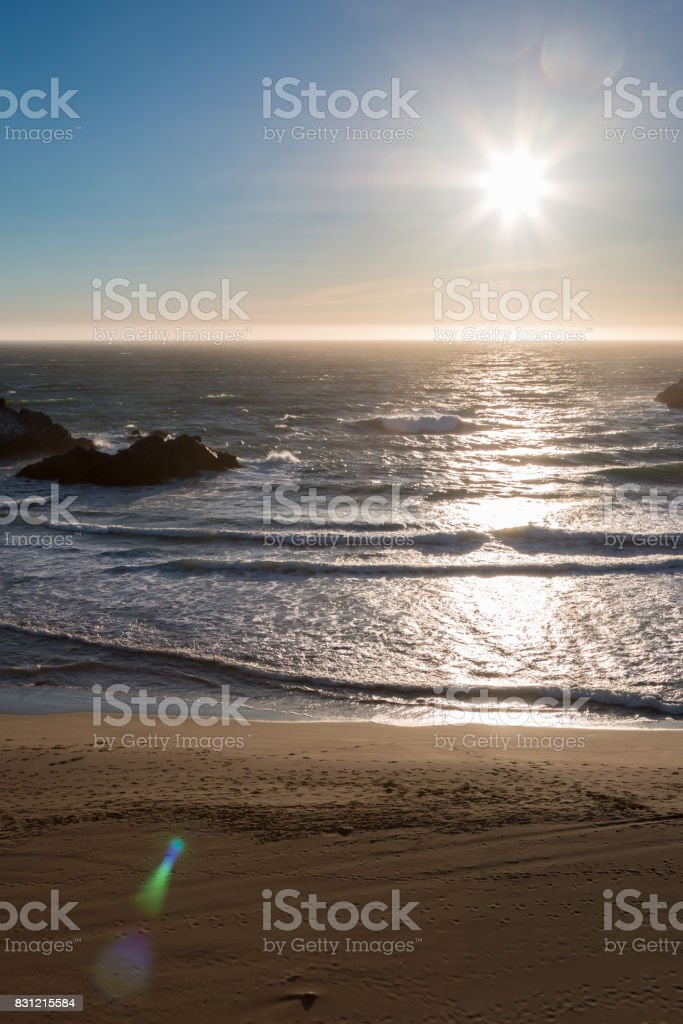 Sunset Over Smooth Sandy Beach with Rocks in the Ocean stock photo