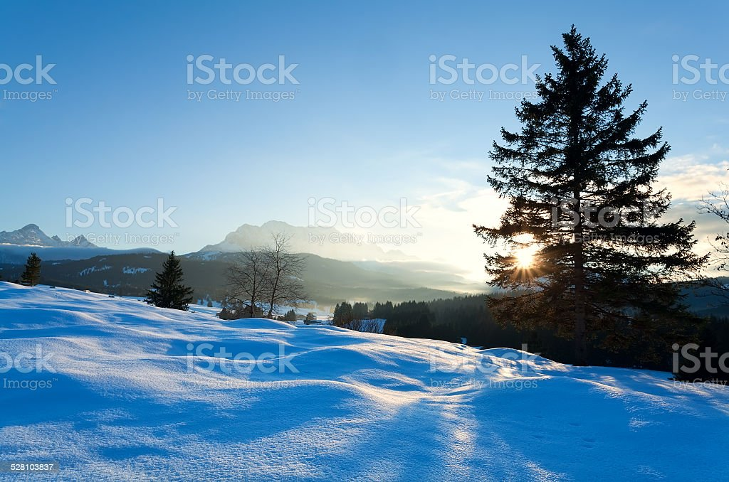 sunset over snowy meadow in Alps stock photo