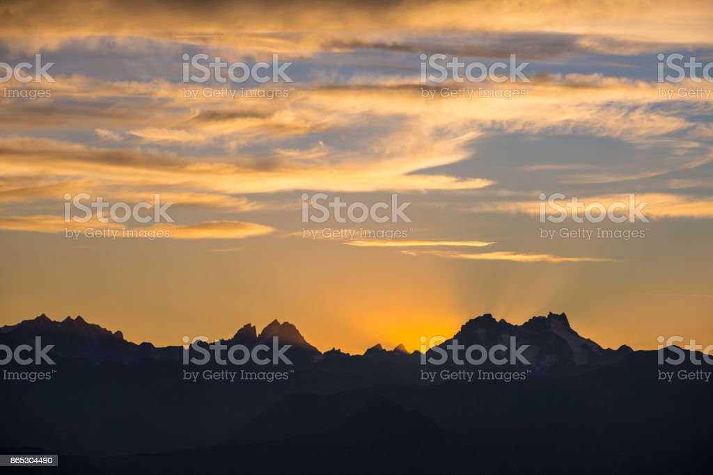 Sunset over the Alps. Colorful sky, high altitude mountain peaks with glaciers, Massif des Ecrins National Park, France. Telephoto view from distant. stock photo