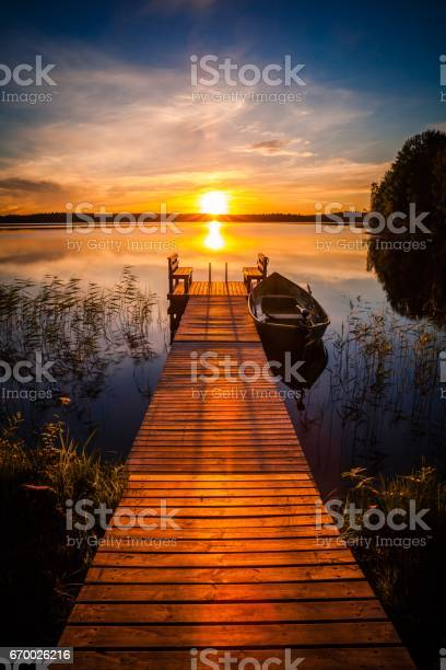 Photo of Sunset over the fishing pier at the lake in Finland