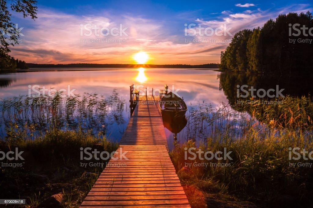 Pôr do sol ao longo do cais de pesca no lago na Finlândia - foto de acervo