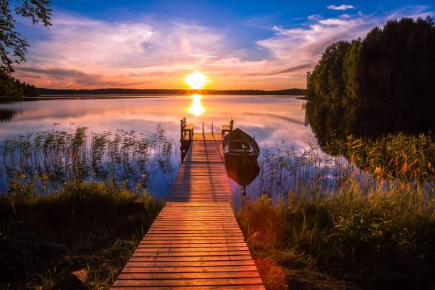 sunset over the fishing pier at the lake in finland - finland stock pictures, royalty-free photos & images