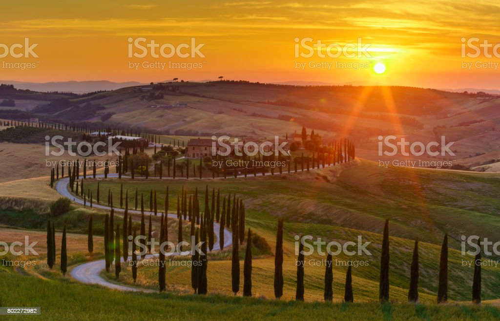 Sunset over the green fields, cypresses trees and winding road in Tuscany, Italy stock photo