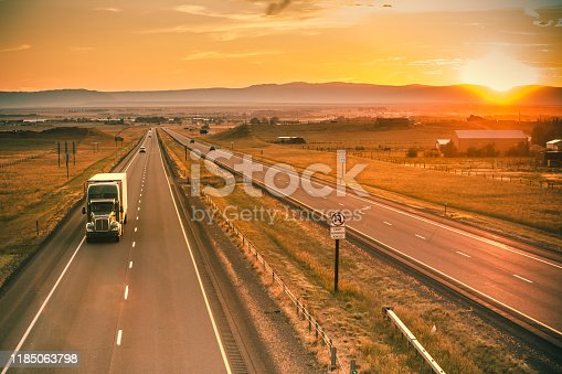Long-haul truck on the Interstate I-80 highway at sunset in Laramie, WYO, USA.
