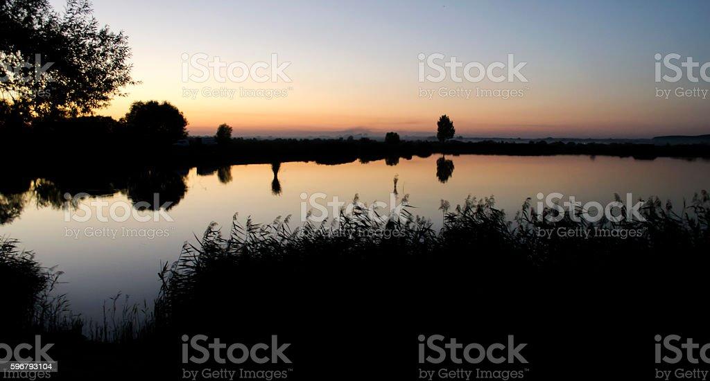 Sunset over the lake fishing stock photo