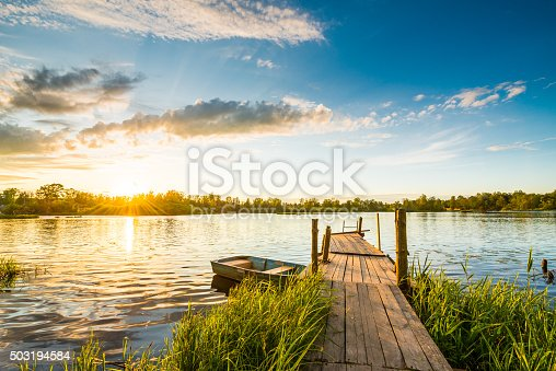 Sunset over the lake in the village. View from a wooden bridge