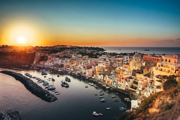 sunset over the marina della corricella, procida island, italy - procida foto e immagini stock