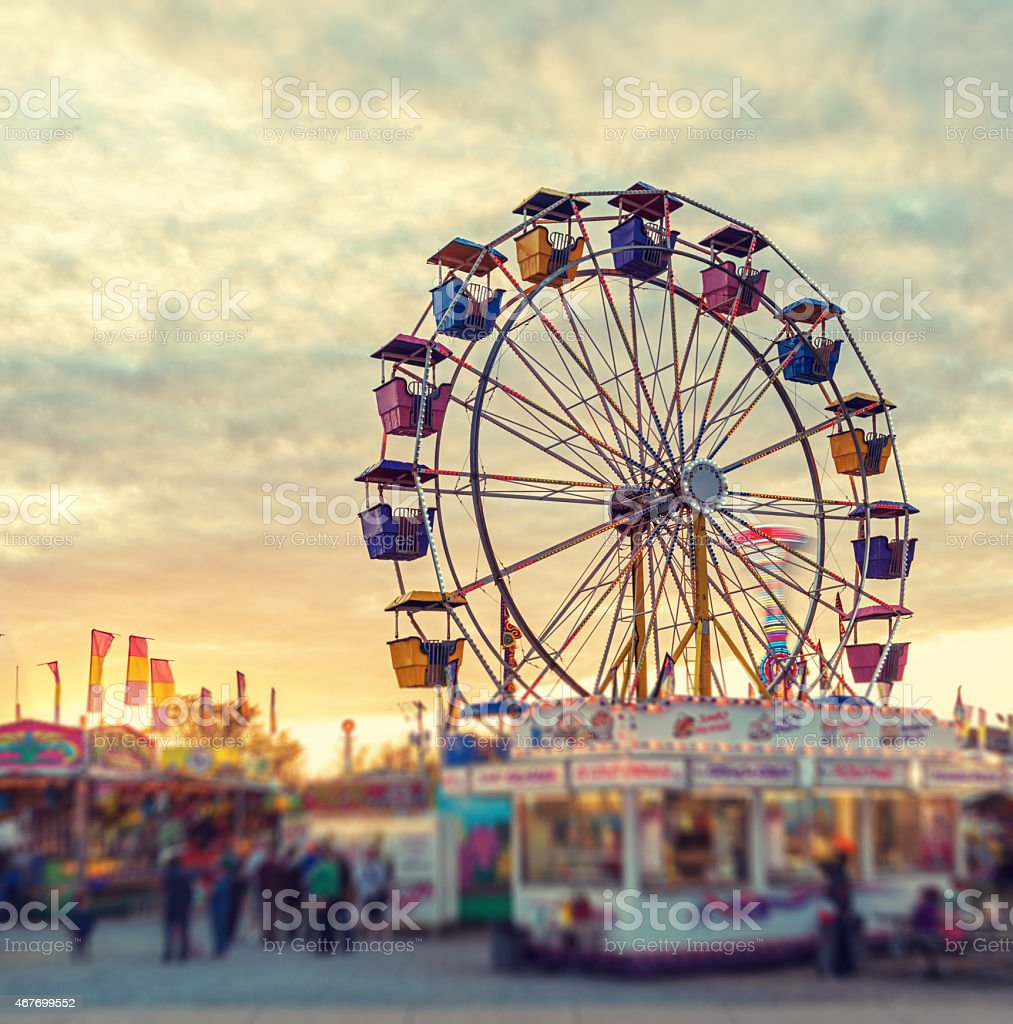 Sunset over the Midway A large ferris wheel pauses to reload in sunset light at a small midway.  Tilt shift lens effect. 2015 Stock Photo