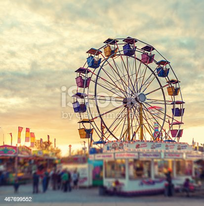 A large ferris wheel pauses to reload in sunset light at a small midway.  Tilt shift lens effect.