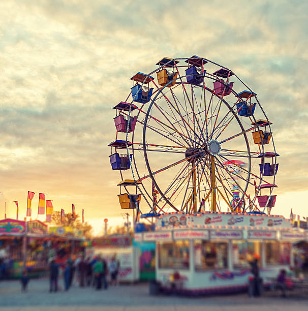Sunset over the Midway A large ferris wheel pauses to reload in sunset light at a small midway.  Tilt shift lens effect. ferris wheel stock pictures, royalty-free photos & images