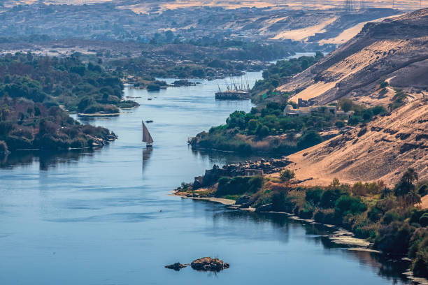 Sunset over the Nile River in the city of Aswan with sandy and deserted shores stock photo