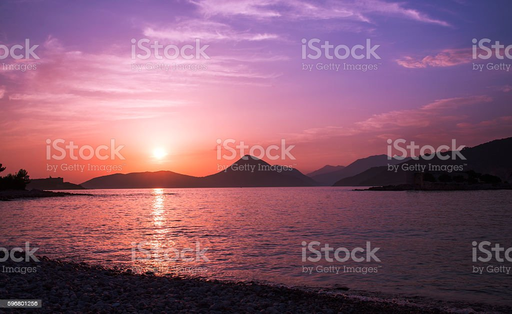 Sunset over the sea and hills stock photo