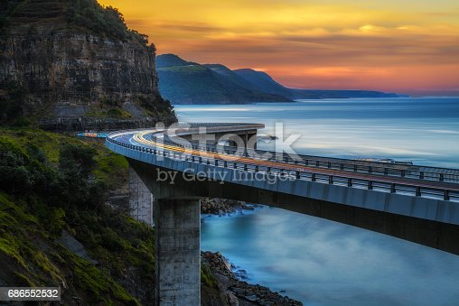 istock Sunset over the Sea cliff bridge along Australian Pacific ocean coast with lights of passing cars 686552532