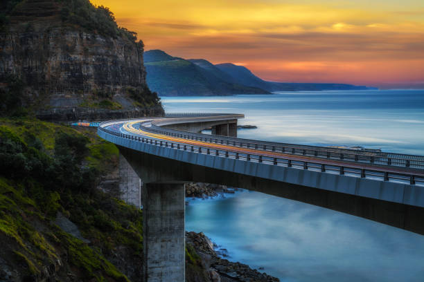 Sunset over the Sea cliff bridge along Australian Pacific ocean coast with lights of passing cars stock photo
