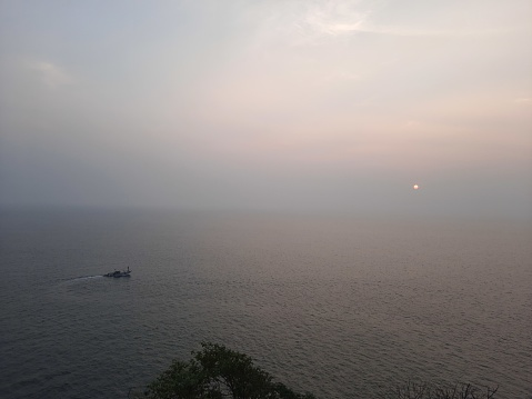 sunset over the sea, fishing boat in the ocean.