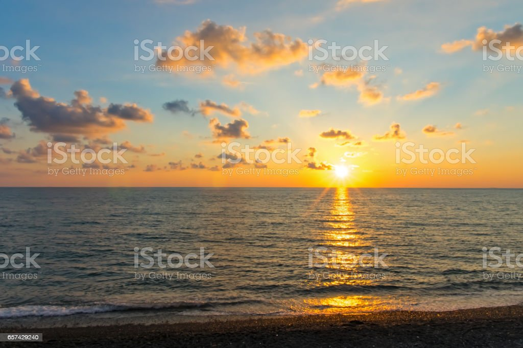 Sunset over the sea in clouds. The sun is from the edge. Blue sky. stock photo