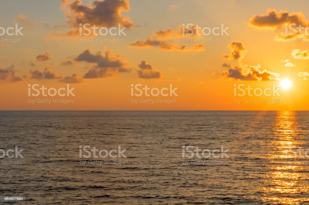 Sunset over the sea in clouds. The sun is from the edge. stock photo