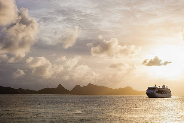 sunset over the sea with a cruise ship in grenadines - passagiersboot stockfoto's en -beelden