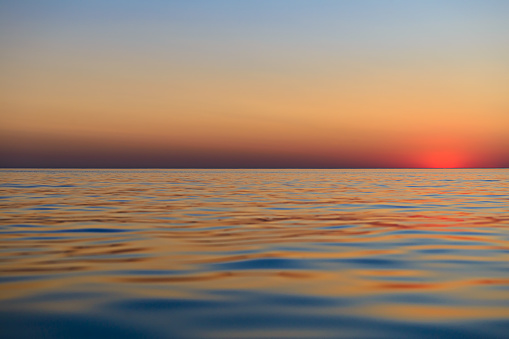 Sunset over the surface of the sea with small waves