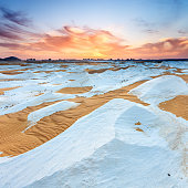 Sunset over  The White Desert, part of The Western Sahara Desert in Egypt. The White Desert of Egypt is located 45 km (28 mi) north of the town of Farafra. The desert has a white, cream color and has massive chalk rock formations that have been created as a result of occasional sandstorm in the area.