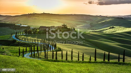Sunset over the winding road with cypresses in Tuscany.