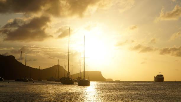 sonnenuntergang über union island mit segelbootyachten in den tobago cays bei saint vincent und den grenadinen, karibik. - kingstown stock-fotos und bilder