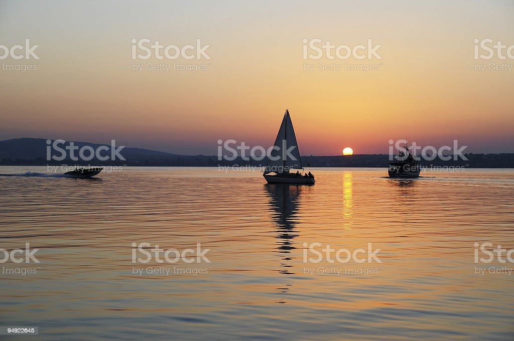 Sunset over water with sailboats  royalty-free stock photo