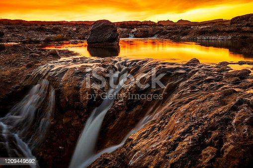 istock Sunset over waterfall in stony environment 1209449592
