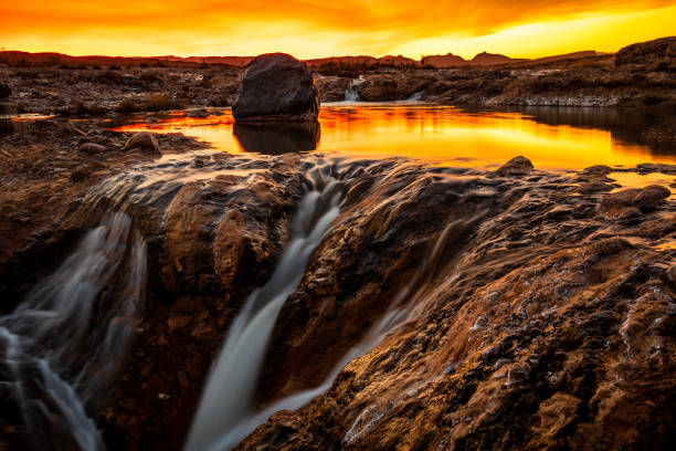 Sunset over waterfall in stony environment stock photo