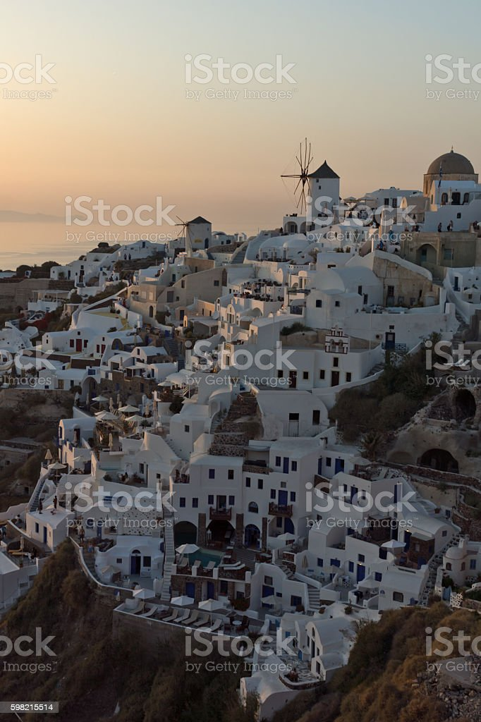 Sunset over white windmills in Oia and panorama to Santorini foto royalty-free