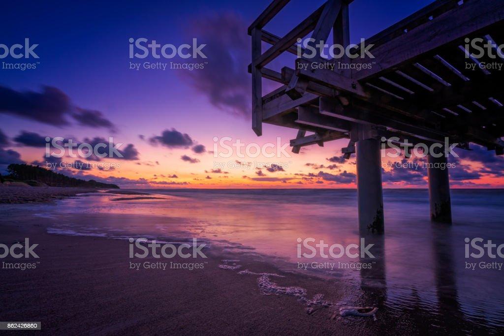 Sunset over wooden pier on the sea beach stock photo