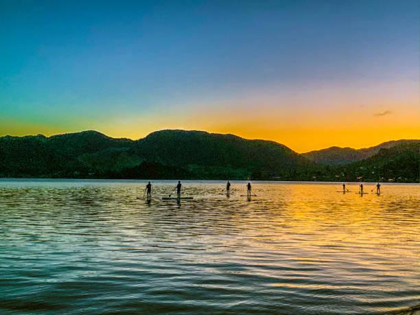 Sunset paddle boarders, Lake Okareka stock photo