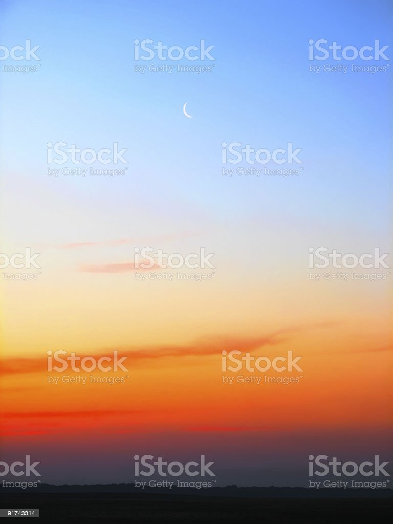 Sunset photo with waning moon and orange and purple sky royalty-free stock photo