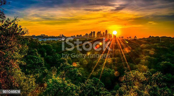 Sunset over Austin , Texas , USA Skyline Cityscape surrounded by greenbelt nature escape Texas Hill Country City in the distance with sun rays and sunbeams at Sunset