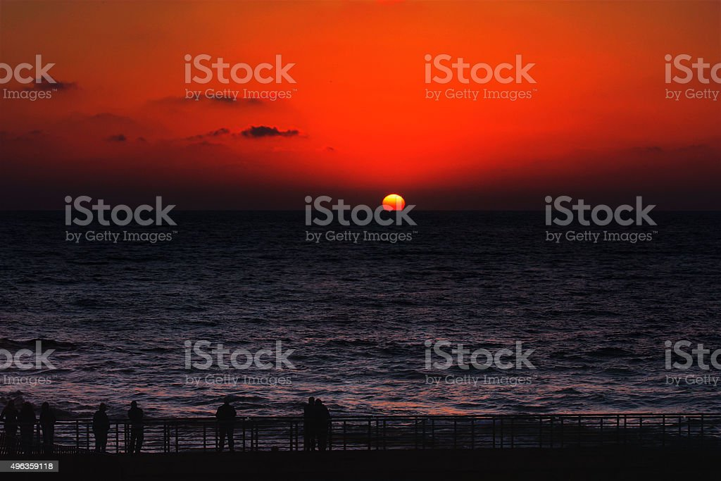 Sunset. Red sun dives into the ocean - inferior mirage stock photo