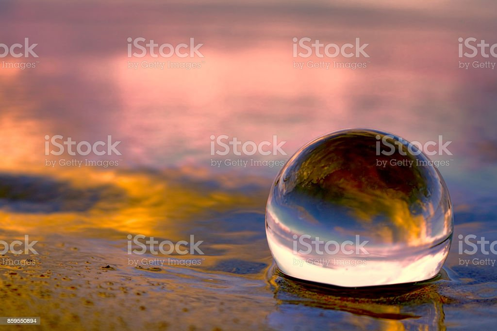 Sunset reflecting in a glass ball on the beach royalty-free stock photo