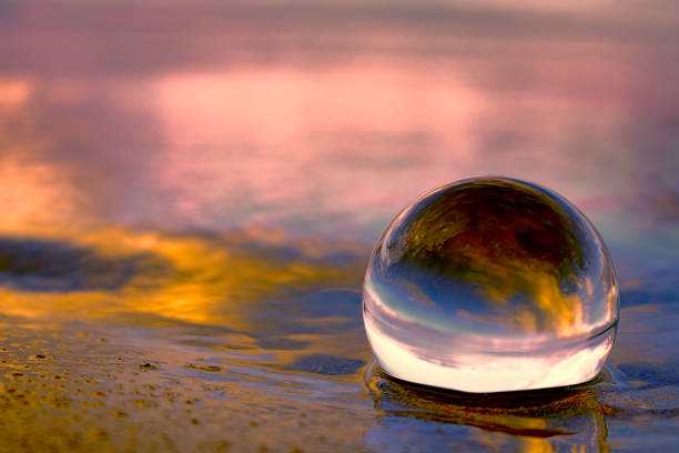 Sunset reflecting in a glass ball on the beach stock photo