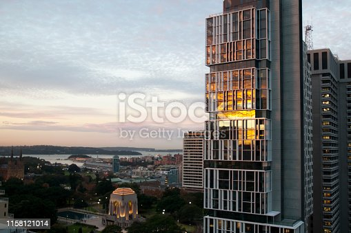 istock Sunset reflecting in glass of highrise apartment building with the Anzac Memorial in Hyde Park and harbour in the background 1158121014
