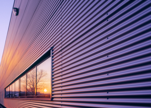 Sunset reflecting in window of newly built warehouse. High-end scan of 6x7cm transparency.