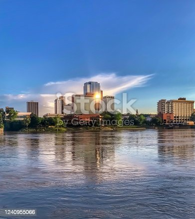 The setting sun is reflected in the skyscrapers along the Arkansas River