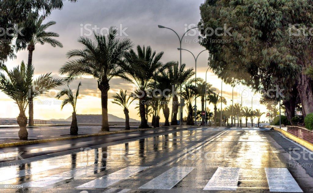 Sunset reflection on wet road at Mediterranean beach stock photo