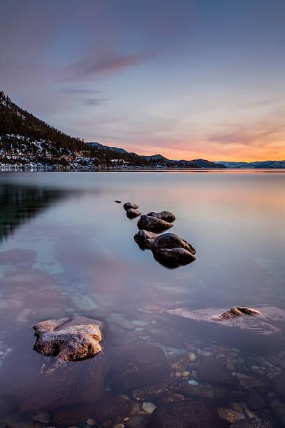 sonnenuntergang reflexion über lake tahoe - lake tahoe winter stock-fotos und bilder